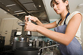 Young woman at stove in kitchen, adding condiment to saucepan
