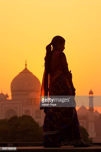 Young woman at sunset with Taj Mahal beyond
