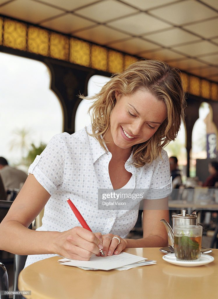 Young woman at table writing on envelope by teapot and glass, smiling : Stock Photo