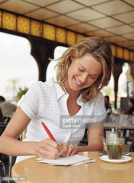 Young woman at table writing on envelope by teapot and glass, smiling
