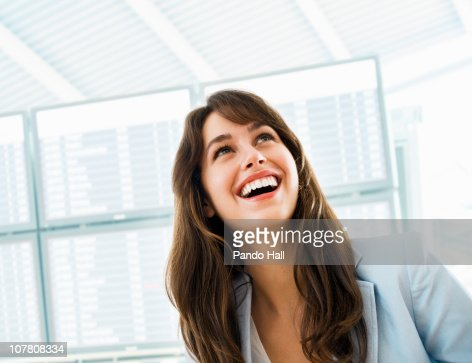 Young woman at the airport, looking up, laughing : Stock Photo