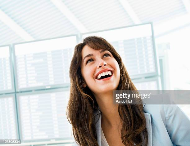 Young woman at the airport, looking up, laughing