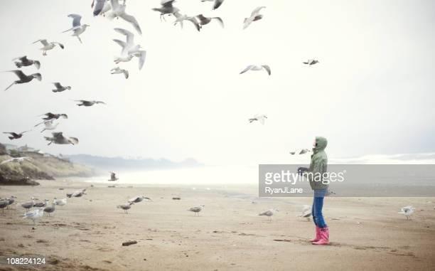 Young Woman at the Beach Feeding Sea Gulls