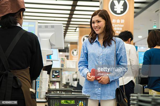 Young woman at the cash register in the supermarket
