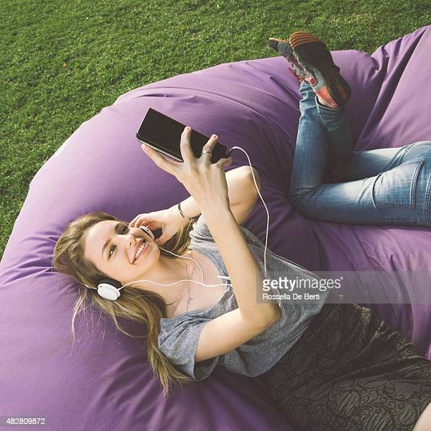 Young Woman At The Park, Listening To Music And Relaxing