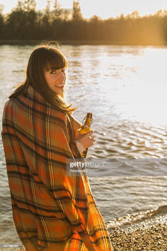 Young woman at the riverside having a beer