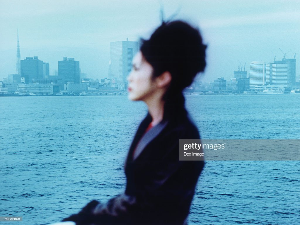 Young woman at waterfront, city in background : Stock Photo