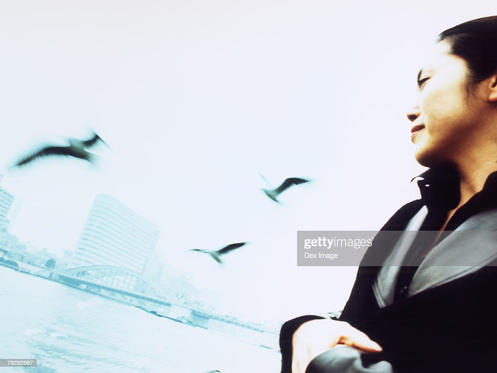 Young woman at waterfront, city in Background, seagulls flying : Stock Photo
