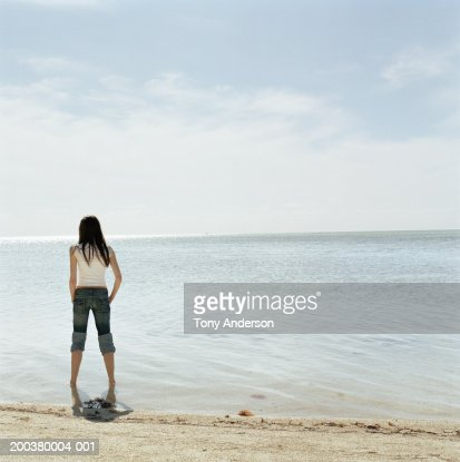Young Woman At Waters Edge At Beach Rear View Stock Photo ...