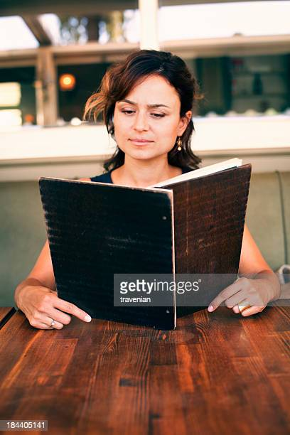 Young woman at wooden table reading a menu