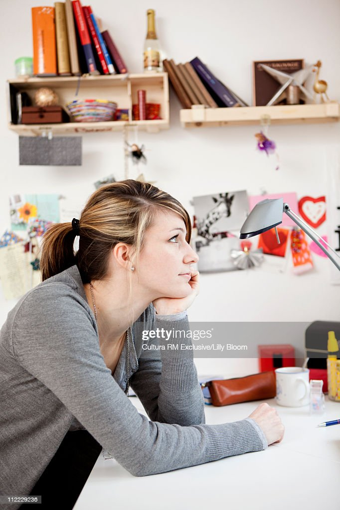 Young woman at writing desk, daydreaming : Stock Photo