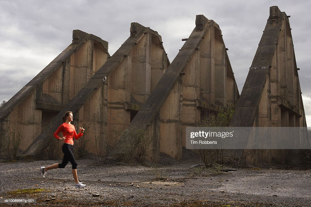 Young woman athlete running by old ruin : Stock Photo