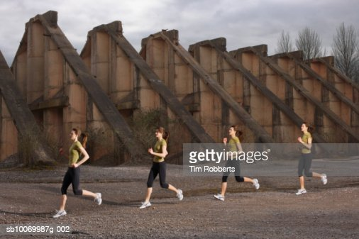 Young woman athlete running by old ruins, multiple exposure : Stock Photo