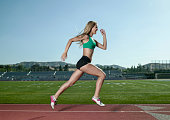 Young woman athlete running on track