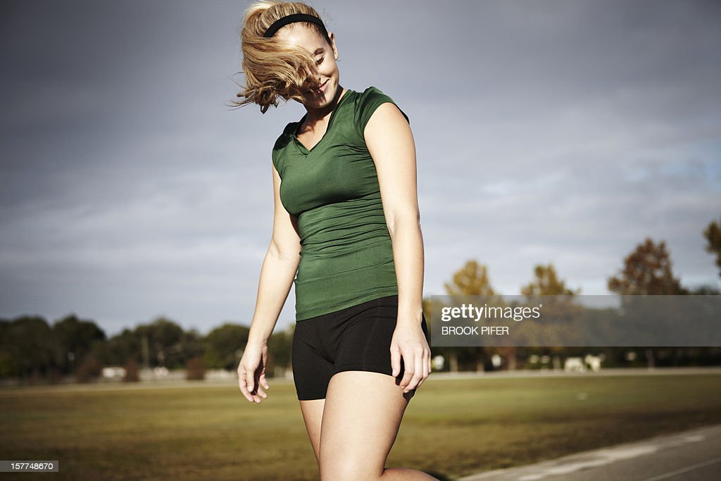Young woman athlete standing on track : Stock Photo