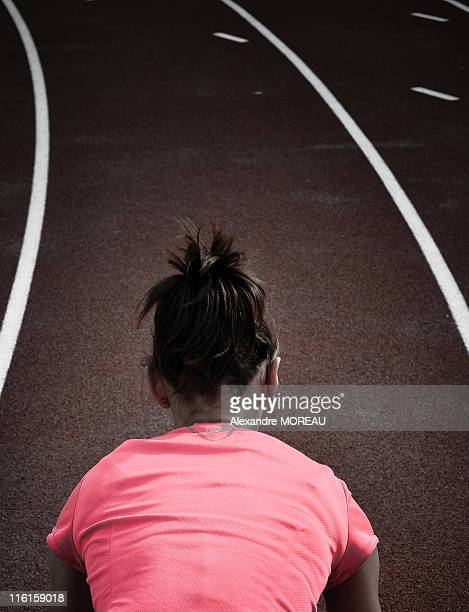 Young woman athlete starting running track race