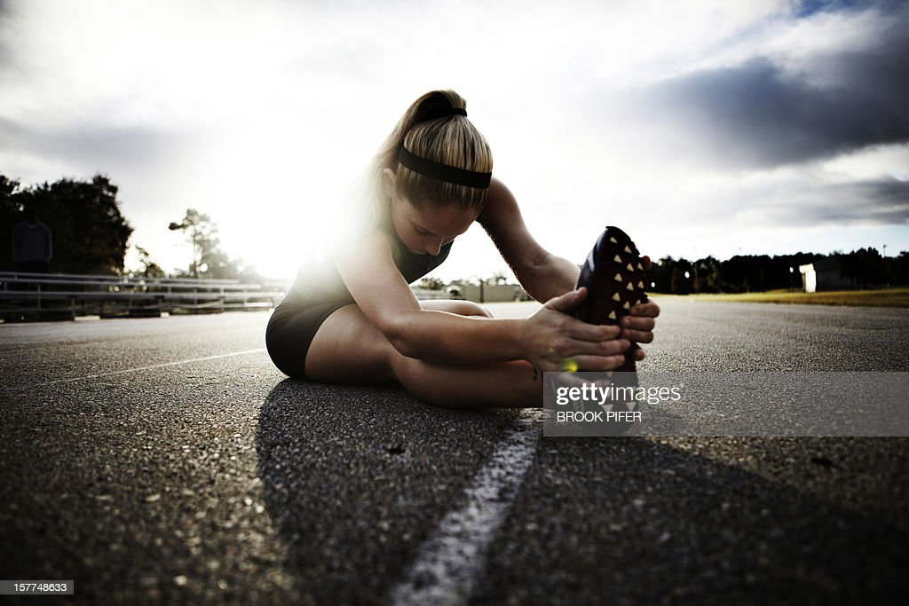 Young woman athlete stretching on track : Stock Photo