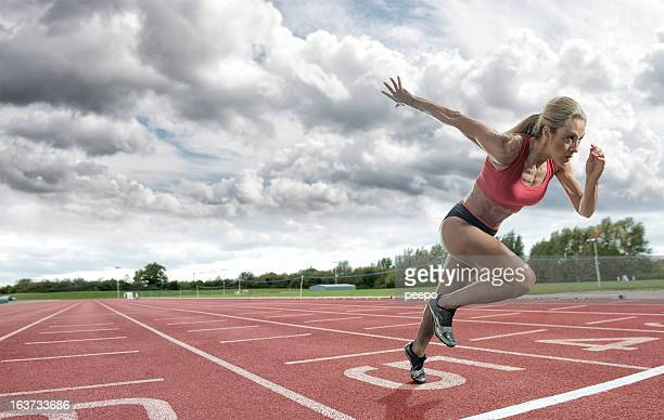 Young woman athlete taking off on a running track