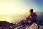 young woman backpacker at sunrise seaside mountain peak