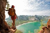 young woman backpacker hiking on seaside mountain