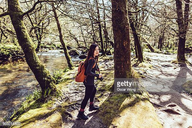 Young woman backpacker walking in forest