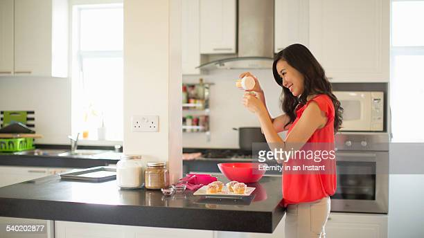 Young woman baking cupcakes in her kitchen,
