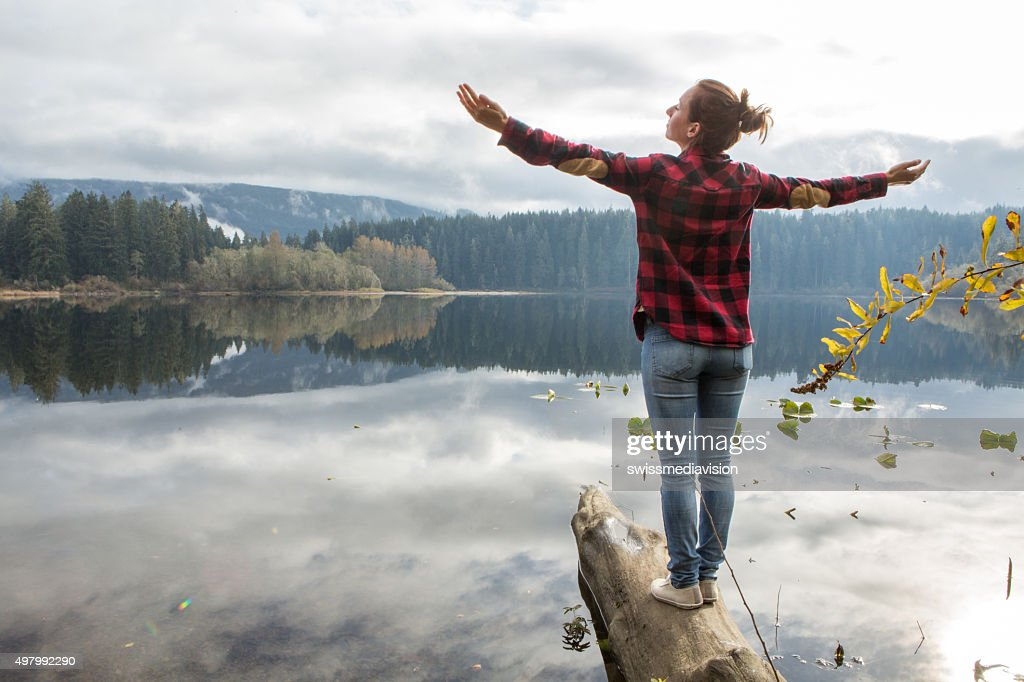 Young woman balances on a tree log above the lake : Stock Photo
