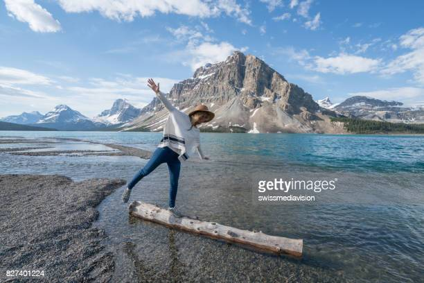 Young woman balances on a tree log above the lake