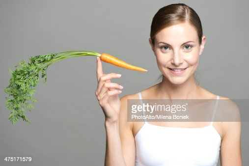 Young woman balancing carrot on fingertip