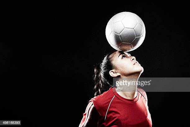 Young woman balancing football on forehead