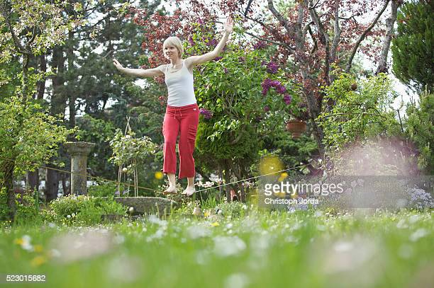 Young woman balancing on a rope in a garden