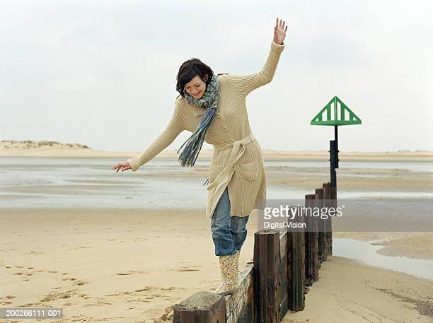 Young woman balancing on groyne, arms outstretched to help balance