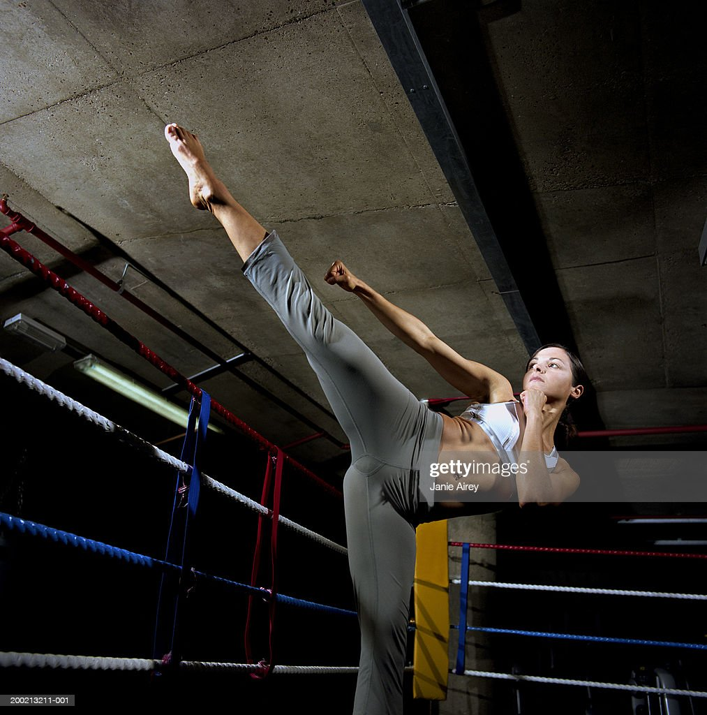 Young woman balancing on one leg in boxing ring, fists raised : Stock Photo