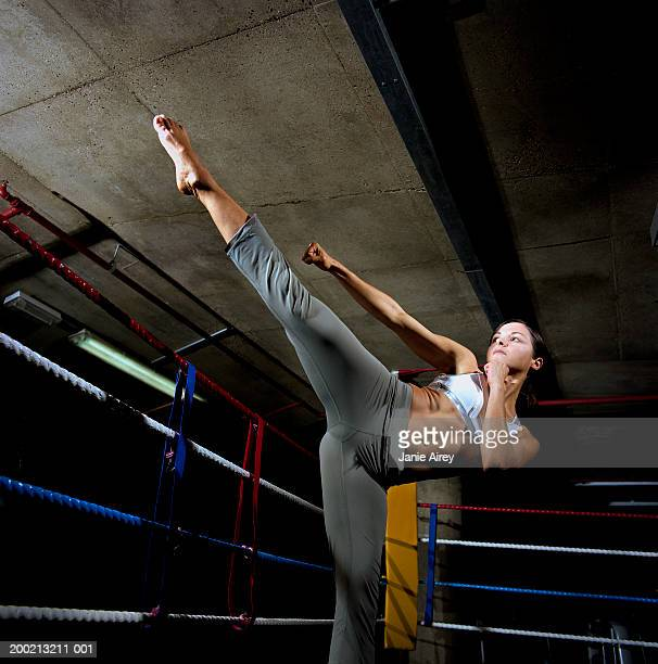 Young woman balancing on one leg in boxing ring, fists raised