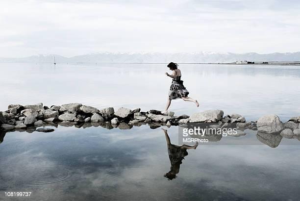 Young Woman Balancing on Rocks in Lake