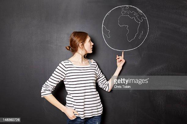 Young woman balancing the world