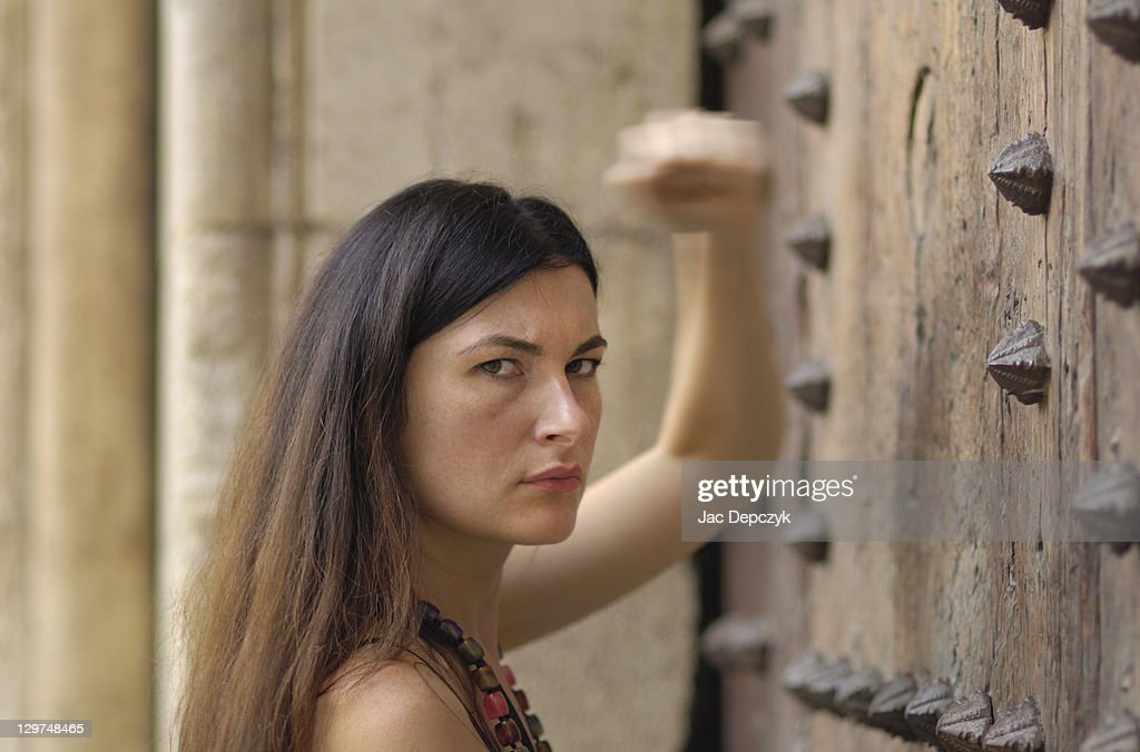 Young woman banging on old heavy gate