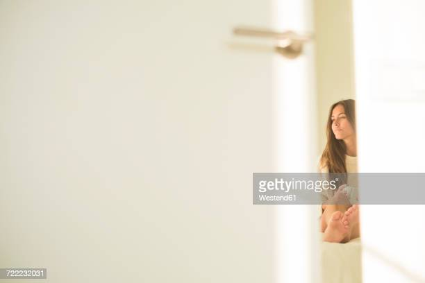 Young woman behind bedroom door sitting on bed with cup of coffee