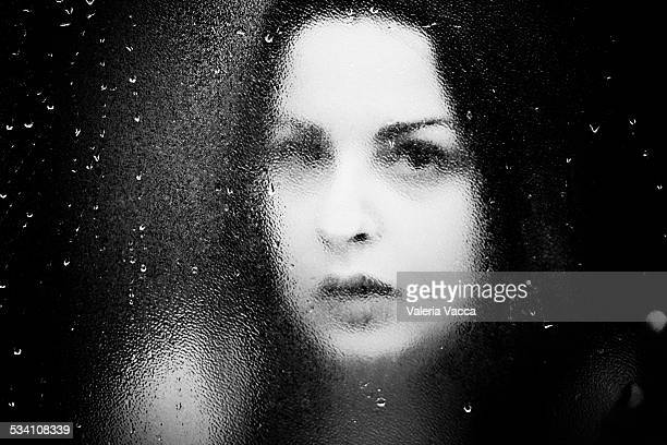 Young woman behind glass with droplets