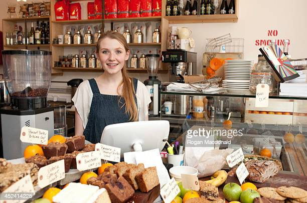 Young woman behind kitchen counter in cafe