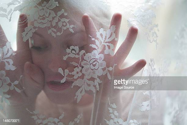 Young woman behind lace curtain