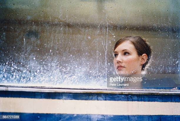 Young Woman Behind Wet Window Pane