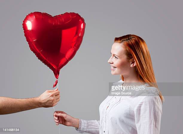 Young woman being given heart shaped balloon