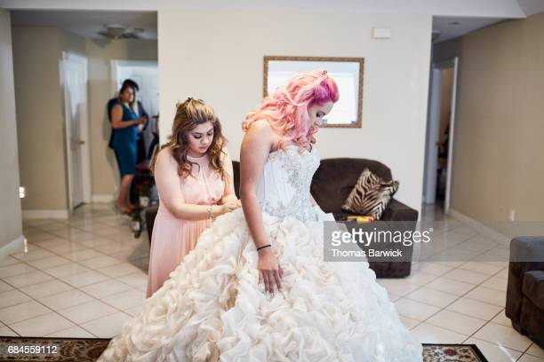 Young woman being helped into quinceanera gown by friend in living room