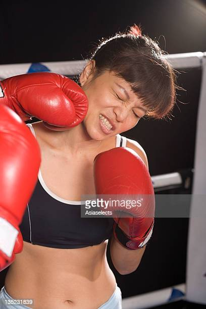Young woman being hit by her opponent in a boxing ring