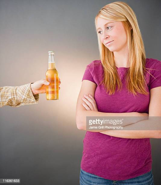Young woman being offered beer