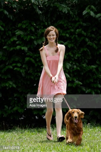 Young woman being pulled by dog on leash : Stock Photo