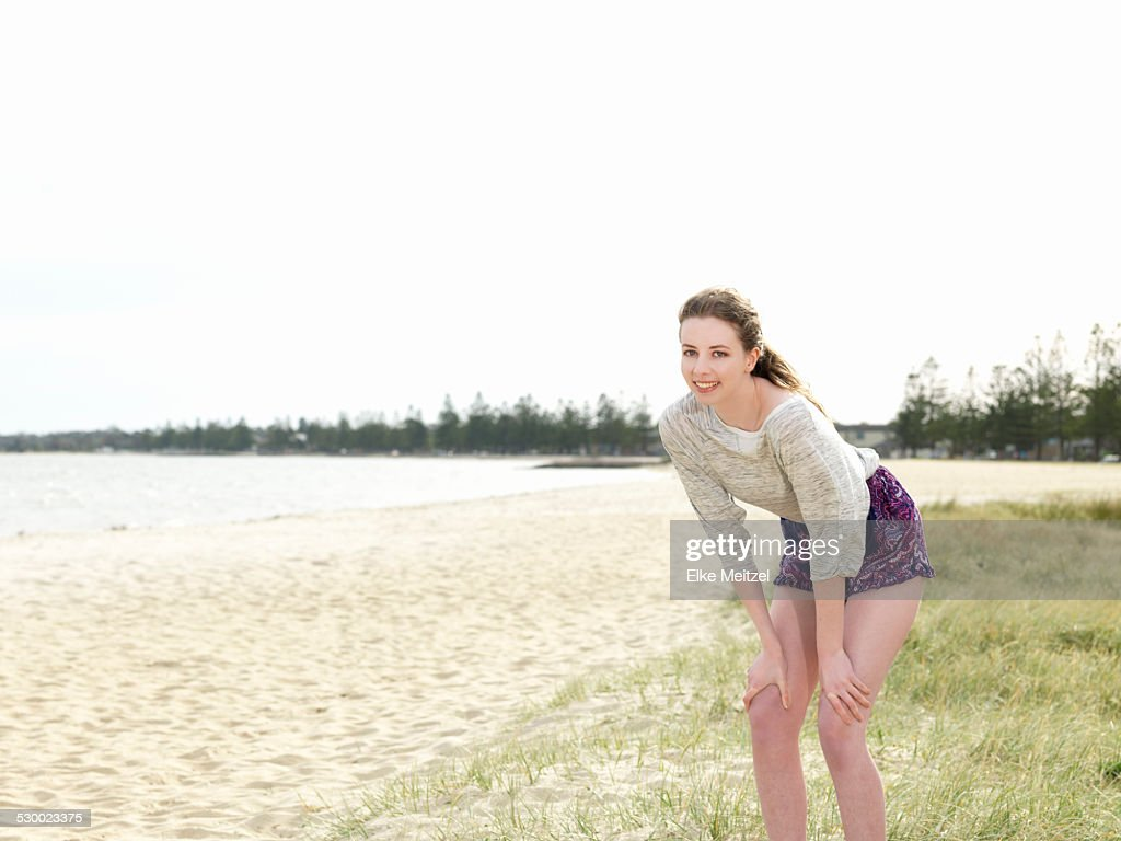 Young woman bending forwards with hands in knees