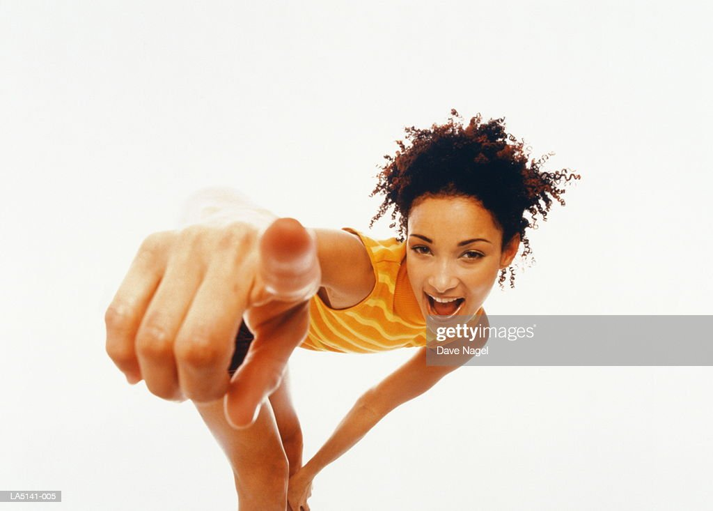 Young woman bending over, pointing finger, portrait (wide angle) : Stock Photo