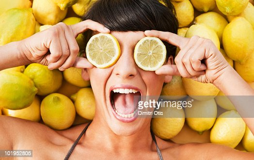 Young woman between lemons holding slices to eyes